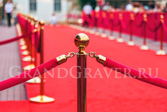 Золотые столбики с канатом и красная ковровая дорожка